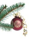 Red Christmas ornament on tree. Red Christmas ornament with gold ribbon hanging from a pine branch isolated on white stock images