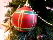 Red Christmas Ornament on Tree. Red and green plaid ornament hanging on a decorated Christmas tree Royalty Free Stock Photos