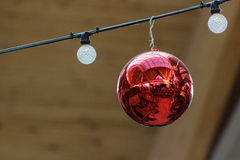 Red Christmas ornamental ball with reflection flanked by lights Royalty Free Stock Images