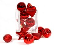 Red Christmas ornaments in and around a glass vase. Isolated on white Royalty Free Stock Photos