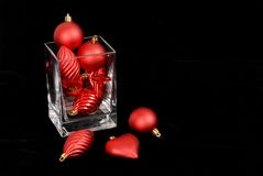Red Christmas ornaments in and around a glass vase. Isolated on black Stock Image