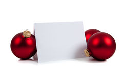 Red Christmas ornaments/baubles with a notecard. Red Christmas ornaments/baubles surrounding a blank notecard on a white background Royalty Free Stock Images