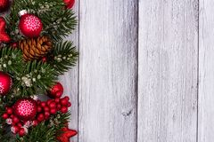 Red Christmas ornaments and branches side border on white wood. Red Christmas ornaments and branches side border on a rustic white wood background Stock Photography