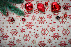 Red Christmas ornaments (cones,balls) and xmas tree on canvas background with red glitter snowflakes. Xmas card. Happy New Year. Space for text Stock Image