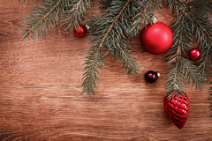 Red Christmas ornaments and fir tree branch on a rustic wooden background. Xmas card. Happy New Year. Top view with copy space Royalty Free Stock Images