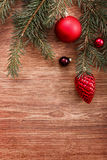 Red Christmas ornaments and fir tree branch on a rustic wooden background. Xmas card. Happy New Year. Top view with copy space Stock Image