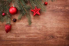Red Christmas ornaments and fir tree branch on a rustic wooden background. Xmas card. Happy New Year. Top view with copy space Royalty Free Stock Photo