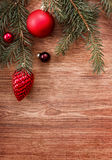 Red Christmas ornaments and fir tree branch on a rustic wooden background. Xmas card. Happy New Year. Top view Stock Photo