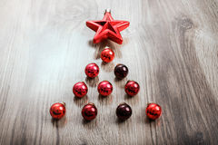 Red Christmas ornaments in the form of a Xmas tree on a rustic wooden background. Merry christmas card. Happy New Year. Top view with copy space Royalty Free Stock Image