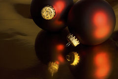 Red Christmas ornaments on gold background Stock Images