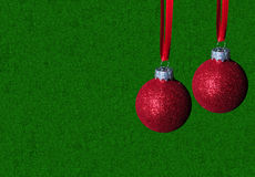 Red christmas ornaments on green background Royalty Free Stock Image