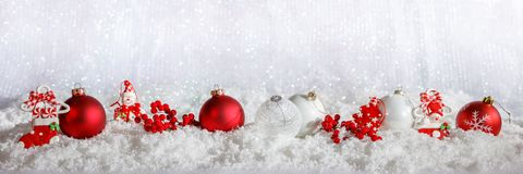 Red Christmas ornaments row on Christmas snowy bokeh background Stock Image