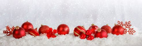 Red Christmas ornaments row on Christmas snowy bokeh background. Red Christmas balls and ornaments on abstract cold winter background with snow stock photo
