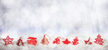 Red Christmas ornaments row on Christmas snowy bokeh background. Red Christmas ornaments on abstract cold winter background with snow Stock Photo
