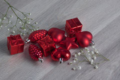 Red Christmas Ornaments. Scattered on a wood background with Babys Breath flowers Royalty Free Stock Photography