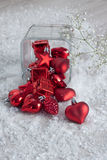 Red Christmas Ornaments on Snow. Red Christmas ornaments spilling out of a glass vase onto snow with Baby's Breath flowers Royalty Free Stock Image