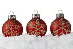 Red Christmas Ornaments With Snowflakes On Snow. Three Red Christmas Ornaments With Golden Glitter Snowflakes On A Bed Of White Snow With Clipping Path Royalty Free Stock Photo
