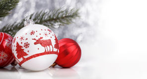 Red Christmas ornaments and xmas fir on canvas background with red glitter snowflakes Royalty Free Stock Photo
