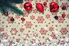 Red Christmas ornaments and xmas tree on canvas background with red glitter snowflakes. Xmas card. Happy New Stock Photo
