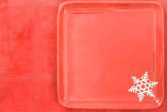 Red Christmas Plate and Tablecloth. Red square Christmas Holiday plate with a with snowflake against a red tablecloth with plenty of copy space Royalty Free Stock Images
