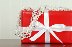 Red christmas present with bead garland Royalty Free Stock Image