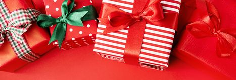 Red Christmas presents on red. From above view of few wrapped beautiful gifts decorated with colorful ribbons and composed on red. Christmas concept. Horizontal stock photography