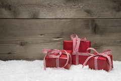 Red Christmas presents with checkered bows on grey wooden backgr. Ound Stock Photo