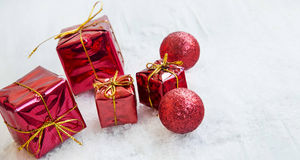 Red Christmas Presents and Glitter Balls in the Snow. Red Christmas Presents Ornaments and Glitter Balls in the Snow Royalty Free Stock Photo