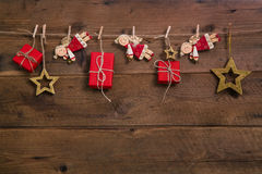 Red christmas presents with golden angels hanging on an old wood. Red christmas gift boxes with golden angels hanging on an old wooden wall Royalty Free Stock Images