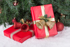 Red Christmas Presents. Red Christmas present on snow against a Christmas tree Royalty Free Stock Photos