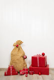 Red christmas presents with santa boots and sack on white wooden Royalty Free Stock Photography