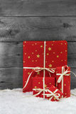 Red christmas presents on wooden background with snow. Royalty Free Stock Image