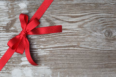 Red christmas ribbon bow on wooden board Stock Photo