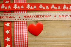 Red christmas ribbon and a love heart Stock Photography