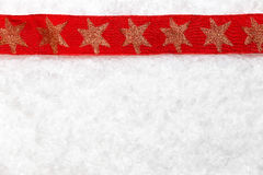 Red christmas ribbon on snowy background Stock Photos