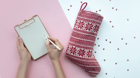 Christmas composition. Christmas hand writing story. Christmas red sock.Pink background, copy space. stock photography