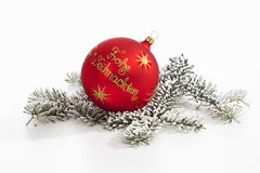Red christmas sphere with golden writing on it on pine twig Royalty Free Stock Images