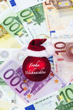 Red christmas sphere with Santa's hat on top on heap of euro notes Royalty Free Stock Photo