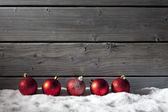 Red christmas spheres on pile of snow against wooden wall Royalty Free Stock Photography