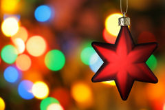 Red Christmas star. Close-up over colorful background Royalty Free Stock Photography