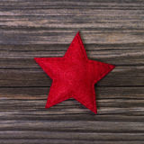 Red christmas star of felt on wooden background for decoration. Stock Images