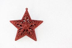 Red christmas star with glittering white background. Stock Photos