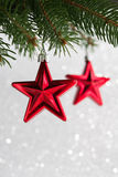 Red christmas stars on the xmas tree on glitter bokeh background. Royalty Free Stock Photos