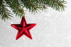 Red christmas stars on the xmas tree on glitter bokeh background. Royalty Free Stock Images