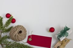 Red Christmas Tags and Twine. Red Christmas tags with twine, bundles of tags and rosemary greens on a white background. Bottom frame justified Royalty Free Stock Photo