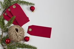 Red Christmas Tags and Twine. Red Christmas tags with twine and rosemary greens on a white background. Frame left justified Stock Image