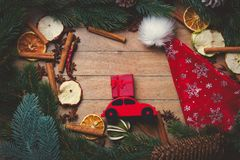 Red Christmas toy car with decoration around. On wooden background Stock Photos