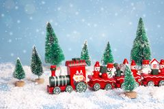 Red Christmas toy train with fir trees and snowfall. Christmas Holiday decorative concept Stock Image
