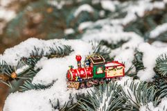 Red Christmas toy train on snowy branch fir. Christmas celebration concept Royalty Free Stock Photography