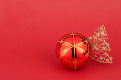 Red christmas tree ball and christmas tree - rote Weihnachtskuge. Red christmas tree ball and christmas tree on red background - rote Weihnachtskugel mit Stock Photo